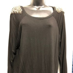 Black sweater with spiked studs on each shoulder.